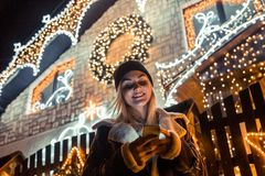 Portrait of beautiful woman using smart phone in front of house. Decorated with Christmas lights royalty free stock photo