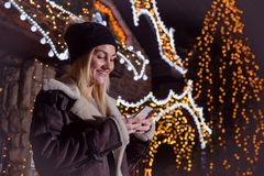 Portrait of beautiful woman using smart phone in front of house royalty free stock image