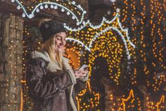 Young woman holding and looking at smart phone in front of house Royalty Free Stock Image