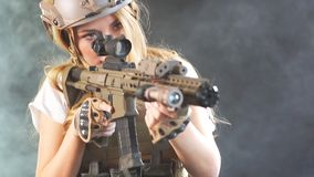 Portrait of a beautiful woman warrior with firearm in hands, aiming at enemy. Slow motion. Portrait of a beautiful woman warrior in military outfit with firearm stock video footage