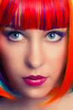 Portrait of a beautiful woman wearing colorful wig Stock Photos