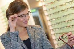 Portrait beautiful woman wearing glasses in optician store. Portrait of beautiful woman wearing glasses in optician store royalty free stock photos