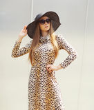 Portrait of beautiful woman wearing a leopard dress, straw hat Royalty Free Stock Images