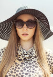 Portrait of beautiful woman wearing a leopard dress, straw hat Stock Photo