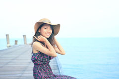 Portrait of beautiful woman wearing long dress and straw hat looking to camera use for people vacation in paradise destination Royalty Free Stock Images