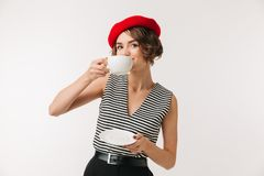 Portrait of a beautiful woman wearing red beret. Drinking tea from cup on a plate isolated over white background Royalty Free Stock Photo