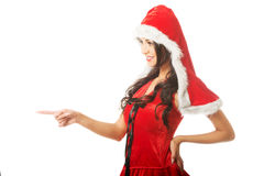 Portrait of beautiful woman wearing santa clothes and pointing to the left Stock Photos
