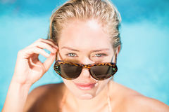 Portrait of beautiful woman wearing sunglasses leaning by poolside Royalty Free Stock Photo