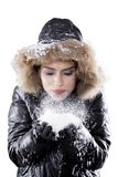 Beautiful woman blowing snow on studio. Portrait of a beautiful woman wearing winter clothes while blowing snow on her palm, isolated on white background Royalty Free Stock Photo