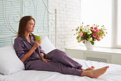 Portrait of beautiful woman on white bed with a cup of tea looki Stock Images