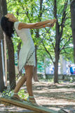 Portrait of a beautiful woman white dress smiling and swinging i. N the forest Royalty Free Stock Photos