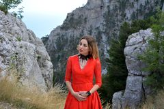 Portrait of a beautiful woman in long red dress in mountains. Ai-Petri mountain. Portrait of a beautiful woman who is watching away in long red dress in Stock Image