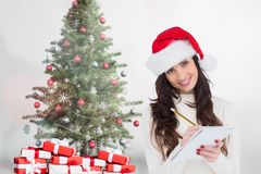 Portrait of beautiful woman writing on notepad. During christmas time Royalty Free Stock Photography