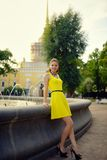 Portrait of the beautiful woman in yellow dress against the fountain Royalty Free Stock Photo