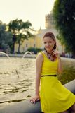 Portrait of the beautiful woman in yellow dress against the fountain Stock Images