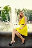 Portrait of the beautiful woman in yellow dress against the fountain Royalty Free Stock Images