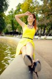 Portrait of the beautiful woman in yellow dress against the fountain Stock Photography