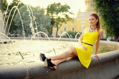 Portrait of the beautiful woman in yellow dress against the fountain Stock Photos