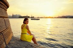 Portrait of the beautiful woman in a yellow dress on the embankment in Sankt Petersburg at sunset Royalty Free Stock Image
