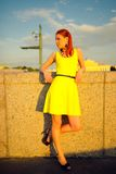 Portrait of the beautiful woman in a yellow dress on the embankment in Sankt Petersburg at sunset Royalty Free Stock Photos
