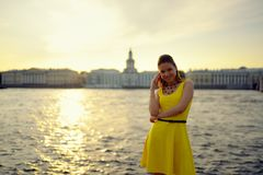Portrait of the beautiful woman in a yellow dress on the embankment in Sankt Petersburg at sunset Stock Photo