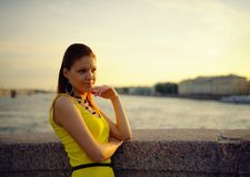 Portrait of the beautiful woman in a yellow dress on the embankment in Sankt Petersburg at sunset Stock Photos