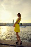 Portrait of the beautiful woman in a yellow dress on the embankment in Sankt Petersburg at sunset Stock Photography