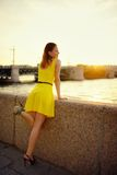 Portrait of the beautiful woman in a yellow dress on the embankment in Sankt Petersburg at sunset Royalty Free Stock Images