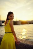Portrait of the beautiful woman in a yellow dress on the embankment in Sankt Petersburg at sunset Stock Image