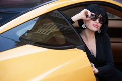 Portrait of a beautiful woman with yellow sports car. Outdoor . Young rich slim girl driver . Lady with black hair wearing sunglasses Spring-summer Royalty Free Stock Images