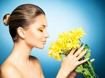 Portrait of beautiful woman and a sunflower over blue background. Spring concept. stock images
