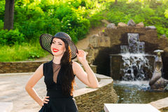 Portrait of a beautiful woman. Portrait of a young beautiful woman in a hat and a black dress near fountain, in park Stock Image