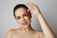 Portrait of Beautiful women holding hand fresh strawberry close her eyes over gray background.Model with light nude make. Portrait of Beautiful woman holding stock photos