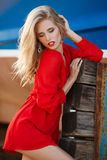 Portrait of beautiful women in old dock. Portrait of the young beautiful smiling woman outdoors enjoying summer sun. Fashion woman in red drees with red lips Royalty Free Stock Images