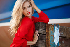 Portrait of beautiful women in old dock. Portrait of the young beautiful smiling woman outdoors enjoying summer sun. Fashion woman in red drees with red lips Royalty Free Stock Photo