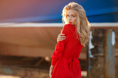 Portrait of beautiful women in old dock. Portrait of the young beautiful smiling woman outdoors enjoying summer sun. Fashion woman in red drees with red lips Royalty Free Stock Image
