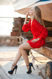 Portrait of beautiful women in old dock. Portrait of the young beautiful smiling woman outdoors enjoying summer sun. Fashion woman in red drees with red lips Stock Photos