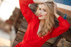 Portrait of beautiful women in old dock. Portrait of the young beautiful smiling woman outdoors enjoying summer sun. Fashion woman in red drees with red lips Stock Images