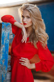 Portrait of beautiful women in old dock. Portrait of the young beautiful smiling woman outdoors enjoying summer sun. Fashion woman in red drees with red lips Stock Image
