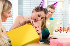 Beautiful woman opening a gift box while celebrating her birthday. Portrait of a beautiful women opening a surprise gift box wrapped in yellow paper while stock photo