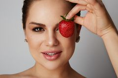 Portrait of Beautiful women smiling and holding hand fresh strawberry close her eyes over gray background.Model with. Portrait of Beautiful woman smiling and royalty free stock photo