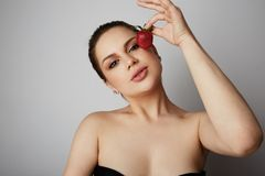 Portrait of Beautiful women smiling and holding hand fresh strawberry close her eyes over gray background.Model with. Portrait of Beautiful woman smiling and stock photo