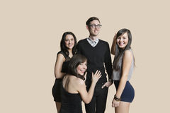 Portrait of beautiful women surrounding mid adult man over colored background Royalty Free Stock Photos