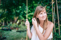 Portrait of the beautiful women  in white dress sitting on the swing in the tropical garden Stock Photo
