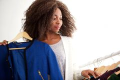 Beautiful young african american woman shopping for clothes at store. Portrait of beautiful young african american woman shopping for clothes at store Stock Photo