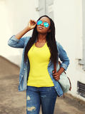 Portrait of beautiful young african woman in colorful clothes. And sunglasses Stock Photo