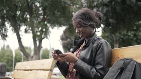 Portrait of beautiful young african woman smiling while sitting outside on a bench holding mobile phone after university Stock Photos