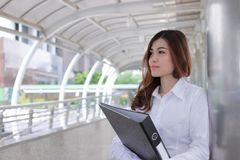 Portrait of beautiful young Asian secretary woman holding ring binder at sidewalk of office with copy space. Portrait of beautiful young Asian secretary woman Royalty Free Stock Images