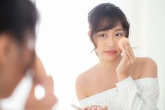 Portrait beautiful young asian woman applying powder puff at cheek makeup of cosmetic looking mirror. Beauty of girl with skin face smile in the bedroom stock images
