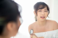 Portrait beautiful young asian woman applying powder puff at cheek makeup of cosmetic looking mirror. Beauty of girl with skin face smile in the bedroom stock photos